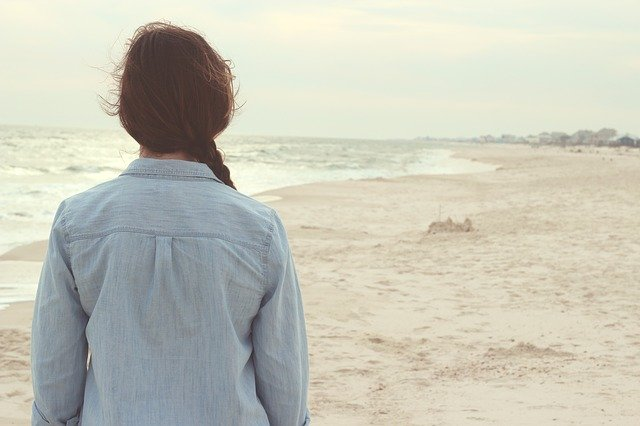 Žena v bielej košeli stojí na pieskovej pláži.jpg