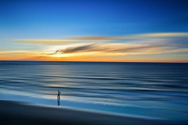 Človek ide po pláži počas svitania.jpg