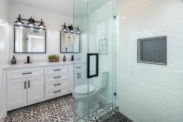 Kúpeľňa s bielym nábytkom, bielymi stenami a sklenenou.jpg
