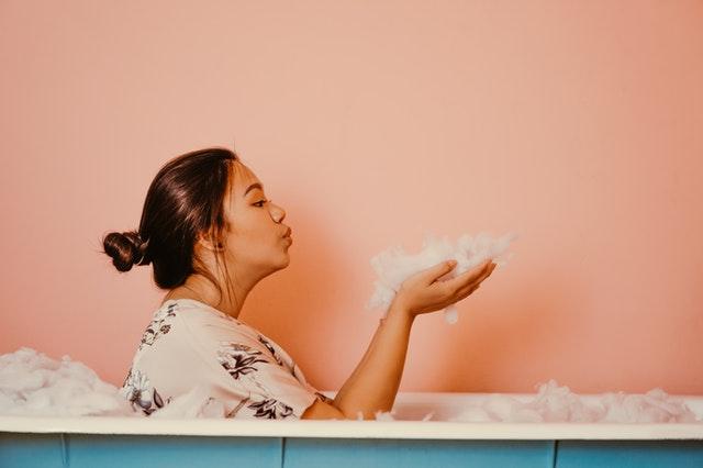 Žena vo farebnom tričku sedí vo vani a fúka do peny.jpg