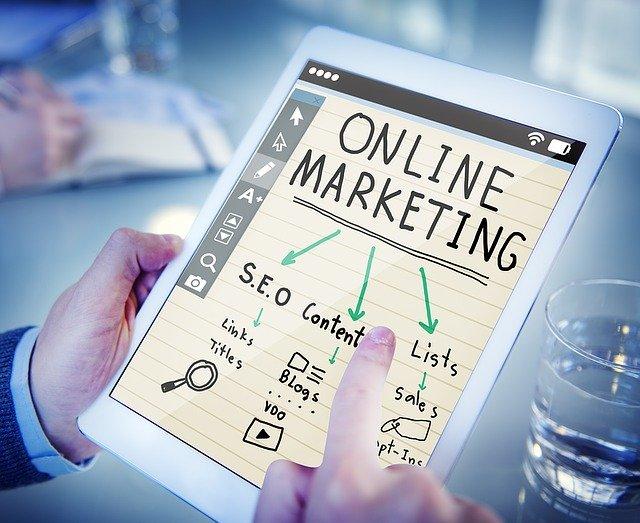 Muž drží  tablet s nápisom online marketing